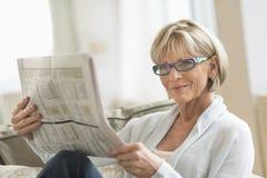 Jornal da leitura da mulher ao relaxar no sofá imagem de stock