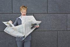 Jornal da leitura da mulher de negócio no tempo ventoso fotografia de stock