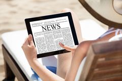 Jornal da leitura da mulher na tabuleta digital na praia Foto de Stock