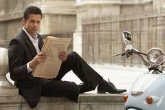Jornal da leitura de Sitting By Scooter do homem de negócios fotografia de stock royalty free