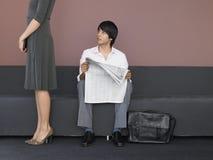 Jornal da leitura de Standing By Businessman da mulher de negócios no sofá Imagens de Stock