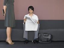 Jornal da leitura de Standing By Businessman da mulher de negócios no sofá Fotografia de Stock Royalty Free