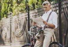 Jornal da leitura do ancião perto da bicicleta no parque imagens de stock royalty free