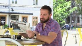 Jornal da leitura do homem e café da manhã comer video estoque