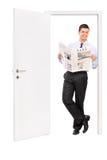 Jornal da leitura do homem e inclinação de uma porta Fotografia de Stock
