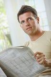 Jornal da leitura do homem em casa foto de stock