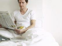 Jornal da leitura do homem na cama imagem de stock