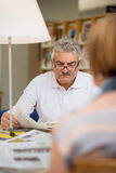 Jornal da leitura do homem sênior com a esposa na biblioteca Fotos de Stock