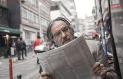 Jornal da leitura do homem superior dentro fora foto de stock