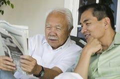 Jornal da leitura do pai e do filho Imagem de Stock