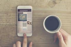 Jornal da leitura do telefone celular que guarda o copo de café foto de stock