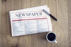 Jornal da leitura e café bebendo no fundo de madeira imagem de stock