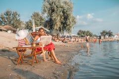 Jornal da leitura da jovem mulher na praia imagem de stock