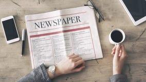 Jornal da leitura da mulher e café bebendo na tabela fotografia de stock royalty free