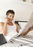 Jornal da leitura na cama fotografia de stock