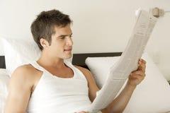 Jornal da leitura na cama imagens de stock