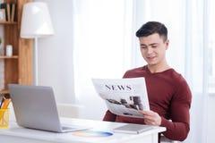 Jornal de exame do freelancer masculino agradável imagem de stock royalty free