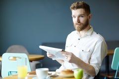 Jornal de manhã considerável da leitura do homem no café fotos de stock royalty free