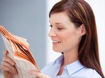 Jornal de sorriso da leitura da mulher de negócios foto de stock