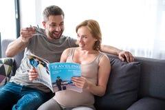 Jornal de viagem da leitura grávida feliz da senhora com marido Imagens de Stock