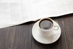 Jornal e xícara de café na tabela fotografia de stock royalty free