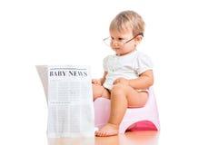 Jornal engraçado da leitura do bebé no chamberpot fotos de stock