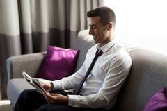 Jornal feliz da leitura do homem de negócios na sala de hotel imagens de stock