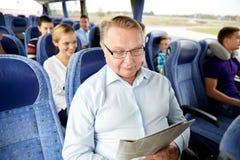 Jornal feliz da leitura do homem superior no ônibus do curso fotos de stock royalty free