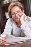 Jornal maduro da leitura da mulher fotos de stock