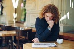Jornal novo da leitura do empresário em um café foto de stock