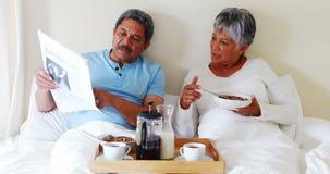 Jornal superior da leitura dos pares ao comer o café da manhã no quarto 4k vídeos de arquivo
