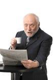 Jornal surpreendido da leitura do homem de negócios foto de stock
