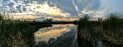 Josh`s Pond in Broomfield Colorado at Sunset reflecting off water, Rocky Mountains in the background Royalty Free Stock Image