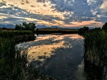 Josh`s Pond in Broomfield Colorado at Sunset reflecting off water, Rocky Mountains in the background Stock Images
