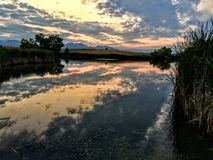 Josh`s Pond in Broomfield Colorado at Sunset reflecting off water, Rocky Mountains in the background Stock Photography