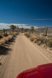 Joshua Tree National Park, California. Red car on single lane dirt road through Joshua Tree National Park, Ca Stock Photo