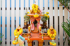Joss house in thailand with flowers in vases and some wreathes.  Stock Photos