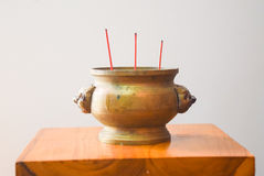 Joss stick pot incense burner with lion statue. On wooden table Stock Images