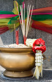 Joss sticks and thai flower garland in incense burner Royalty Free Stock Photography