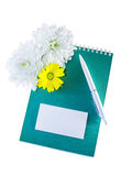 Jotter, card, pen and flowers Royalty Free Stock Images