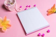 Jotter em um fundo cor-de-rosa com ornamento das mulheres Dia do `s do Valentim fotos de stock royalty free