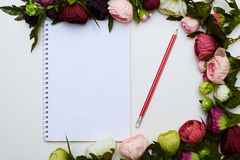 Jotter and red pencil circled by colorful flowers Stock Photos