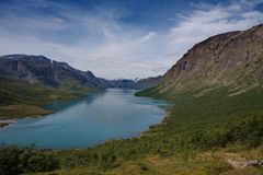 Jotunheim norway. The natural park Jotunheim, Norway provides stunning landscapes. This blue colored lake is surrounded by arching rock formations and green royalty free stock photos