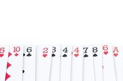 Jouant des cartes avec différents nombres et couleurs dans la ligne d'isolement Image libre de droits