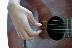 Jouant la guitare d'isolement sur le blanc Image stock