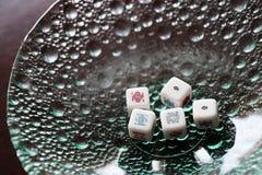 Jouant, le tisonnier cinq découpe dans un bol en verre Image libre de droits