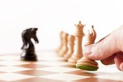 Jouant les échecs - pièces d'échecs mobiles de main sur un échiquier Photos stock