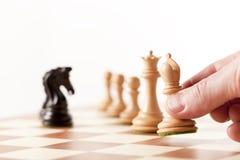 Jouant les échecs - pièces d'échecs mobiles de main sur un échiquier Image stock