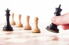 Jouant les échecs - pièces d'échecs mobiles de main sur un échiquier Image libre de droits