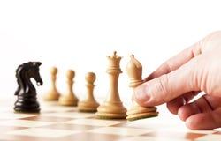 Jouant les échecs - pièces d'échecs mobiles de main sur un échiquier Photo stock